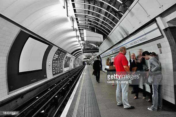 People waiting for train at the underground King's Cross St Pancras tube station. Railway tracks, leading lines, vanishing point, perspective,...