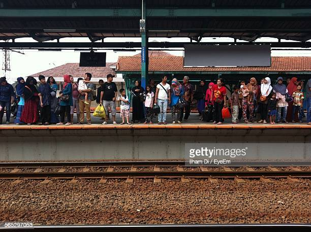 People Waiting For Train On Railroad Station In City