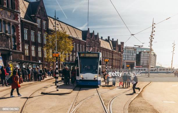 Mensen wachten op tram voorzijde van het Amsterdam Centraal station