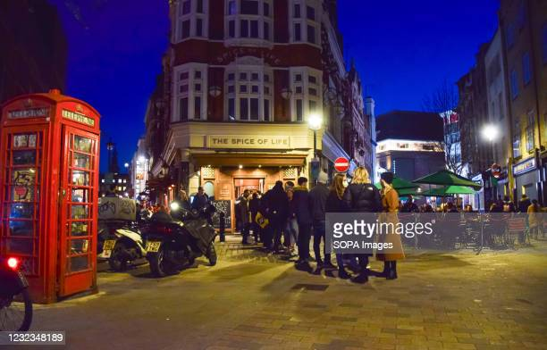 People waiting in a queue outside The Spice Of Life pub in Soho. Crowds of people packed the bars and restaurants in Soho, Central London, on the...