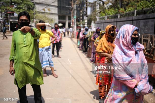People waiting in line at a shop run by the government in Bangladesh They were seen to be keeping distance while standing in lines to prevent the...