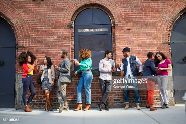 people waiting in line at theater using cell phones - lining up stock pictures, royalty-free photos & images