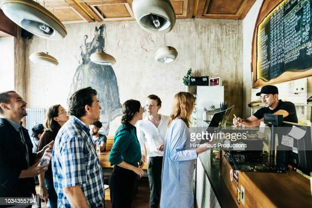 people waiting in line in busy burger restaurant - restaurant stock pictures, royalty-free photos & images