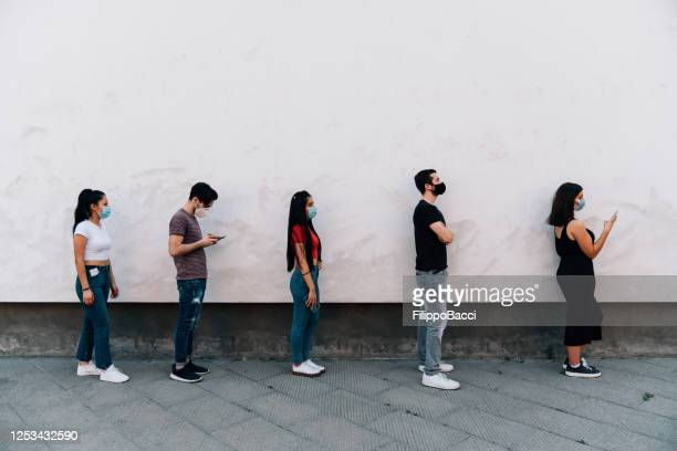 people waiting in line to enter in a store - social distancing concept - distant stock pictures, royalty-free photos & images
