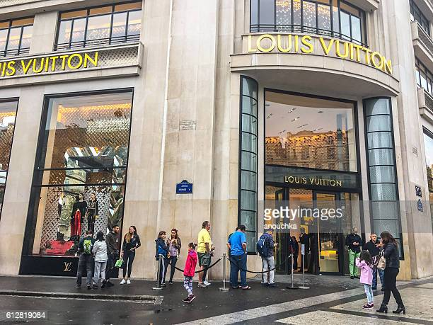 people waiting in line to enter louis vuitton, paris, france - louis vuitton designer label stock photos and pictures
