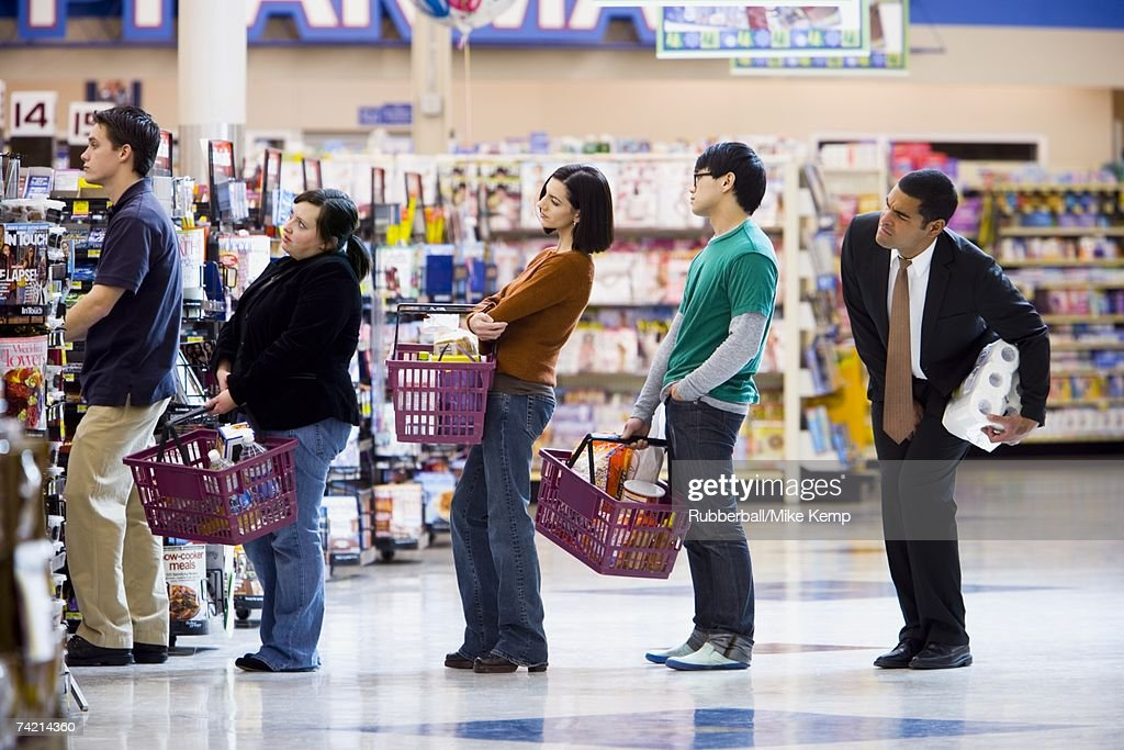 People waiting in line with shopping baskets at grocery store : Stock Photo