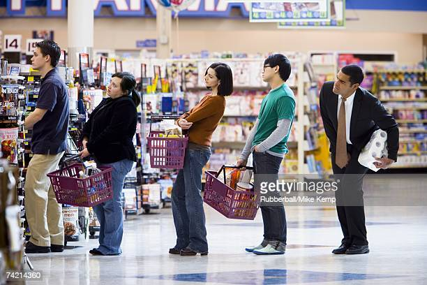 people waiting in line with shopping baskets at grocery store - lining up stock pictures, royalty-free photos & images
