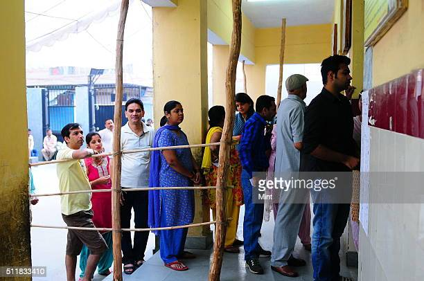 People waiting in queue at a polling booth to cast their vote for general election of the 16th Lok Sabha 2014 on April 10 2014 in New Delhi India