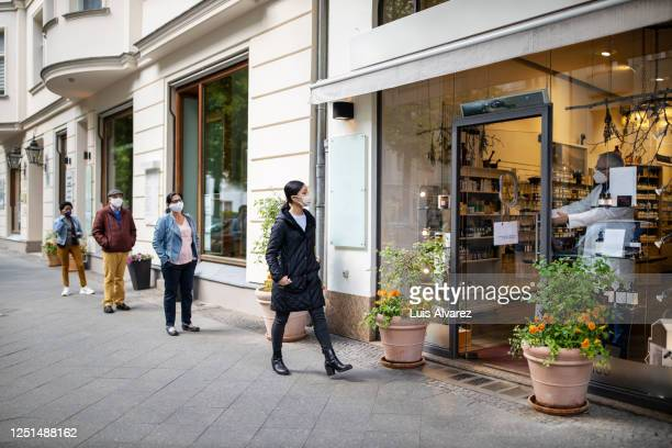 people waiting in the queue outside pharmacy with social distancing - distant stock pictures, royalty-free photos & images