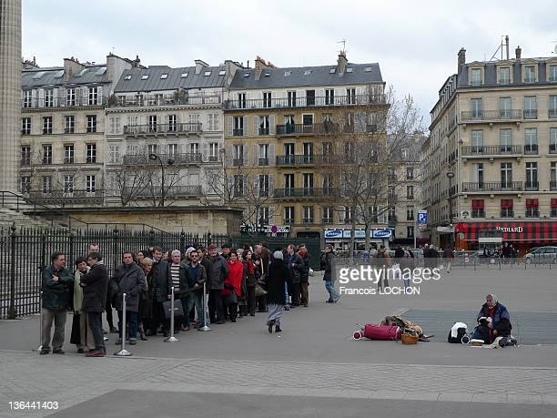 People waiting on a line and an homeless woman sitting near them on Madeleine Square on March 7 2009 in Paris France