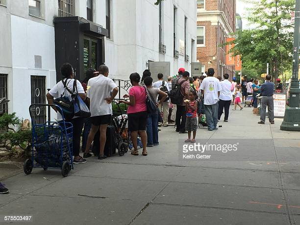 People waiting on line on the sidewalk in the Fort Greene neighborhood of Brooklyn, NYC to get free food from a community food-drive location -...