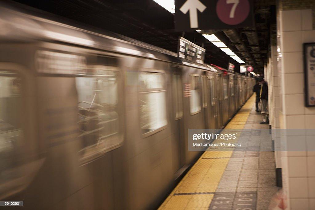 People waiting on subway platform as train goes by, New York City, NY, USA : Stock Photo