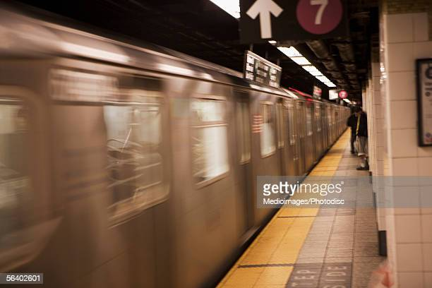 People waiting on subway platform as train goes by, New York City, NY, USA