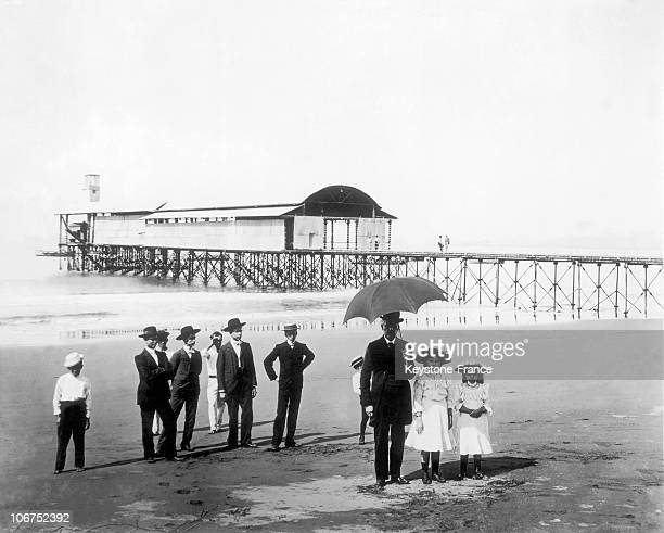 People Waiting On The Beach Of Puntarenas In Costa Rica Around 19101920 A Hangar For Planes Including Those Of The Panamerican Airline Is Seen In The...
