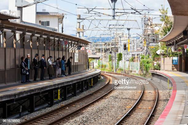People waiting on train platform in Kyoto, Japan