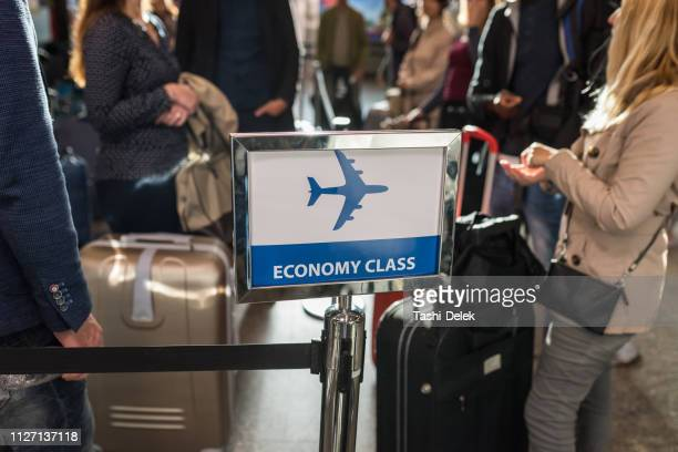people waiting to board to economy class airplane - balkans stock photos and pictures