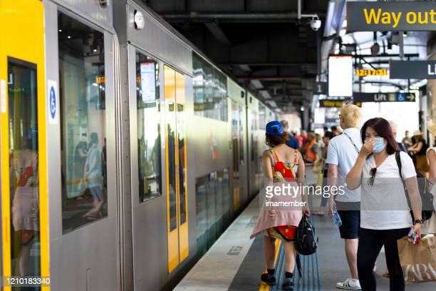 people waiting to board train at subway station wearing face mask, copy space - coronavirus australia stock pictures, royalty-free photos & images