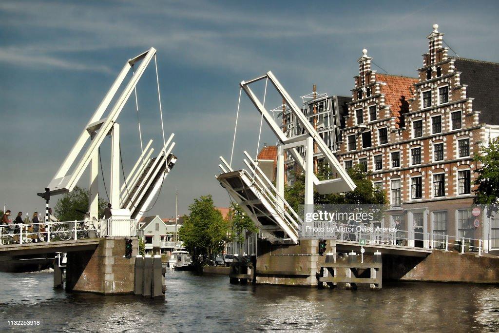 People waiting to cross over the Gravestenenbrug drawbridge lifted on the Spaarne River in Haarlem, Netherlands : Foto de stock
