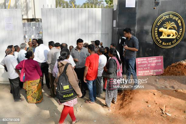 People waiting to exchange demonitised Indian currency make enquiries at the closed gates of Reserve Bank of India in Bangalore on January 2 2017...