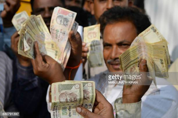 People waiting to exchange demonitised Indian currency show their old 500 and 1000 Rupee notes near the closed gates of Reserve Bank of India in...
