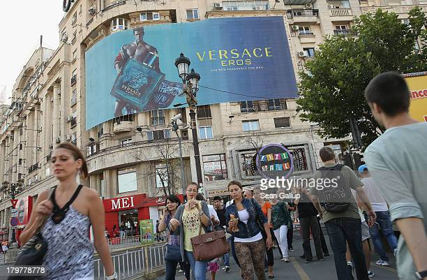 People wak past a Versace advertisement in the city center on September 6 2013 in Bucharest Romania While the country's economic output has risen...