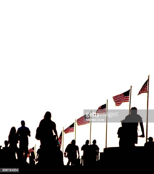 People waking into a sunset amongst backlit american flags.