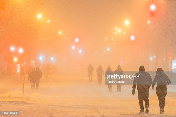 People walk 2nd Ave. during Snowstorm at Night.
