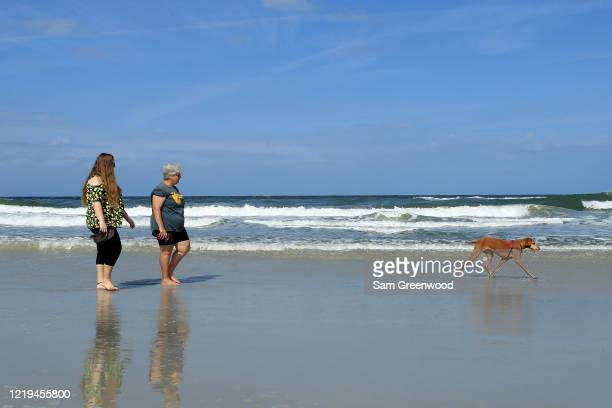 People walk a dog on the beach on April 17 2020 in Jacksonville Beach Florida Jacksonville Mayor Lenny Curry announced Thursday that Duval County's...