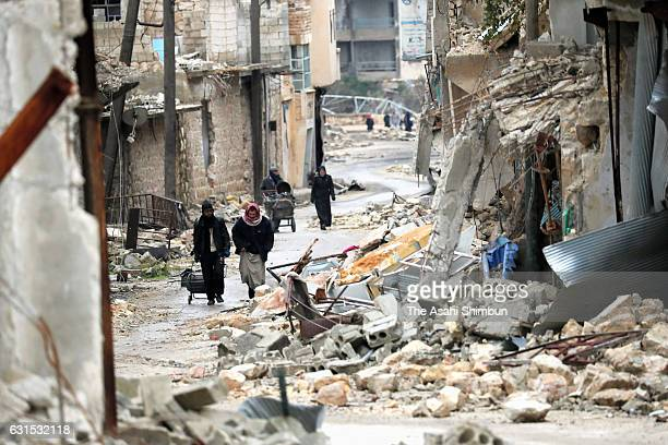 People walk a street on January 10 2017 in Aleppo Syria Bashar alAssad administration backed by Russia recaptured the area in eastern Aleppo where...