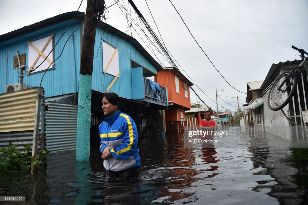 TOPSHOT - People walk accros a flooded street in Juana Matos, Puerto Rico, on September 21, 2017 as the country faced dangerous flooding and an island-wide power outage following Hurricane Maria. /