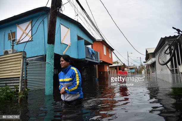 TOPSHOT People walk accros a flooded street in Juana Matos Puerto Rico on September 21 2017 as the country faced dangerous flooding and an islandwide...