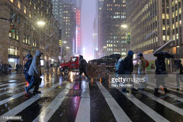 People walk across 7th Avenue in front of Times Square as a snow squall passes through Manhattan on December 18 in New York City