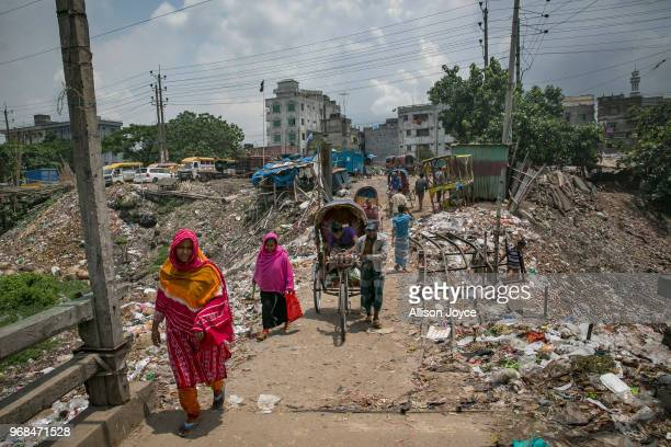 People walk across a bridge above a canal which empties into the Buriganga river on June 3 2018 in Dhaka Bangladesh Bangladesh has been reportedly...
