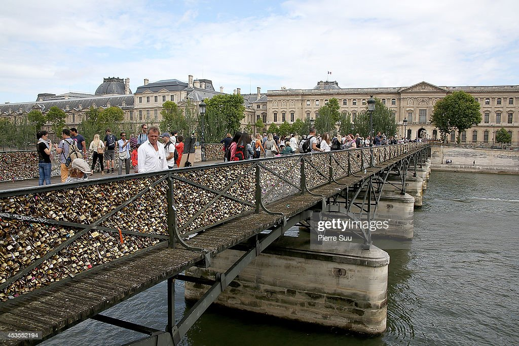 People walk across a bridge filled with 'love locks' as tourists are being encouraged to post 'selfies' online instead of attaching padlocks to Paris bridges on August 12, 2014 in Paris, France. Paris officials are reportedly encouraging couples to cease the padlock tradition as bridges face weight concerns over potential collapse.