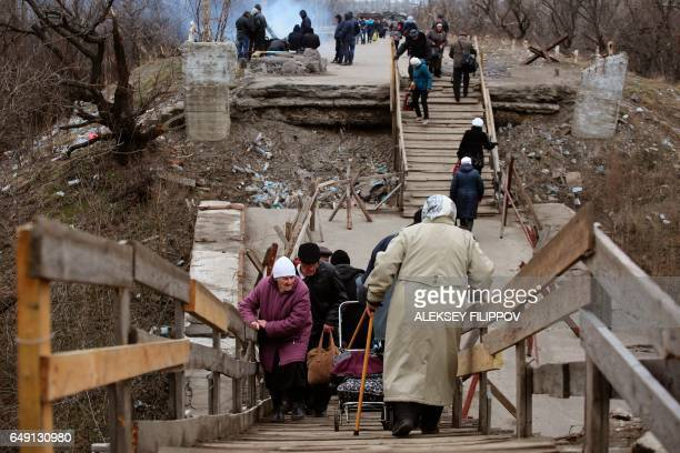 People walk across a destroyed bridge into Ukrainecontrolled territory at a checkpoint guarded by proRussian rebels in Stanytsia Luhanska Lugansk...