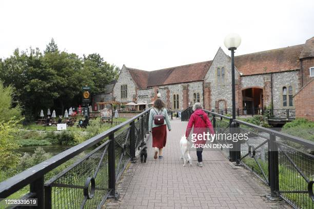 People walk across a footbridge over the River Avon heading toward the Bishop's Mill pub in Salisbury southern England on September 4 2020 that was...