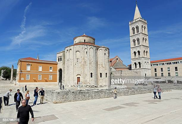 People walk across a square in front of Church of St Donatus on April 21 2016 in Zadar / AFP / STRINGER