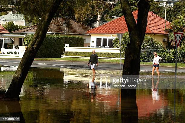People walk across a submerged road next to Narrabeen Lake on April 22 2015 in Sydney Australia Three people have died and more than 200000 are still...
