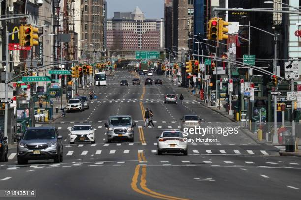 People walk across a virtually empty Canal St on Easter Sunday on April 12, 2020 in New York City.