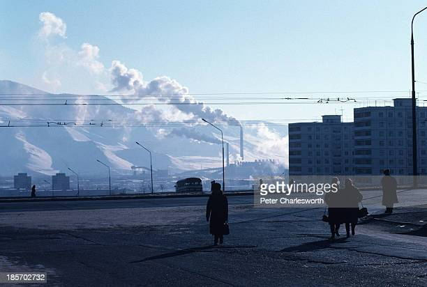 People walk across a wide street on the edge of the capital, Ulan Bator. In the background can be seen apartment buildings built by the Soviet Union...