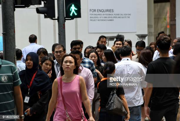 People walk across a zebra crossing at a light in the financial business district in Singapore on February 14 2018 / AFP PHOTO / Roslan RAHMAN