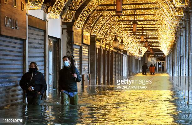 """People walk across an arcade by a flooded St. Mark's Square on December 8, 2020 in Venice following a high tide """"Alta Acqua"""" event following heavy..."""
