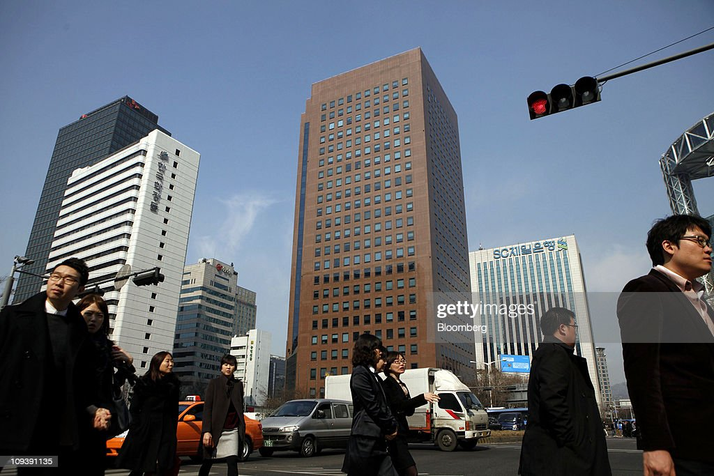 People walk across an intersection in front of the YoungPoong Building, center, which houses the Deutsche Bank AG office, in Seoul, South Korea, on Thursday, Feb. 24, 2011. Deutsche Bank AG was given the heaviest penalty ever levied on a foreign securities firm in South Korea for triggering a Nov. 11 stock market rout that erased $26 billion of value. Photographer: Jean Chung/Bloomberg via Getty Images