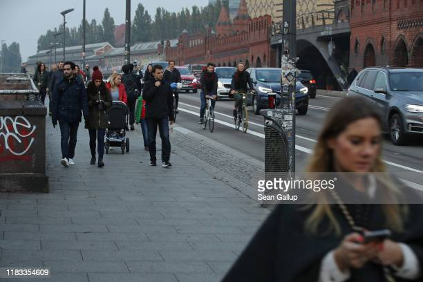 People walk across Oberbaumbruecke bridge on October 24, 2019 in Berlin, Germany. This photo pairs for a then-and-now comparison with image asset...