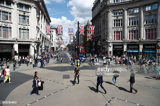 People walk across oxford Circus as Union flags hang across Oxford Street in central london on June 27 2016 Shares in banks airlines and property...