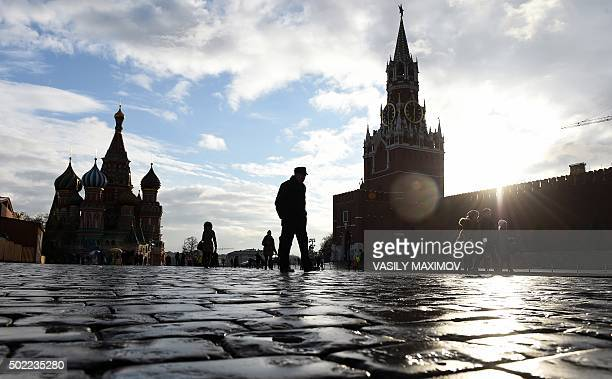 People walk across Red Square with the Kremlin's Spasskaya Tower and St Basil's Cathedral seen in the background in central Moscow on December 22...