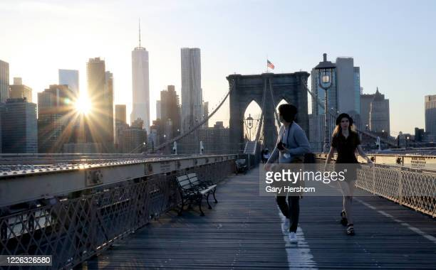 People walk across the Brooklyn Bridge as the sun sets on May 21, 2020 in New York City .