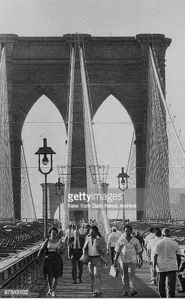 People walk across the Brooklyn Bridge from Brooklyn to Manhattan during the 1977 blackout power failure