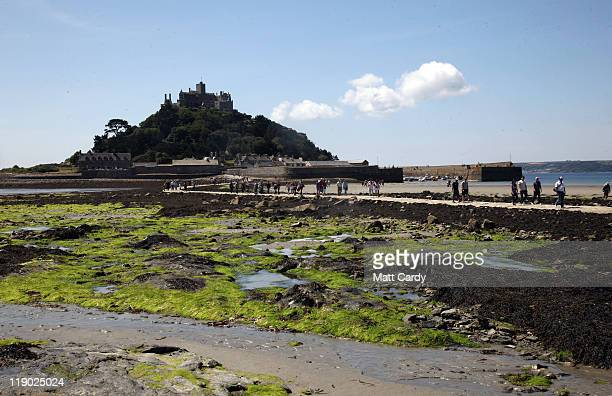 People walk across the causeway to St Michaels Mount at low tide on July 14, 2011 in Penzance, England. With many state schools about to break for...
