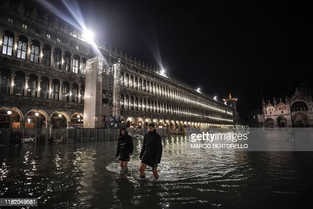 People walk across the flooded Piazza San Marco square during an exceptional Alta Acqua high tide water level on November 12 2019 in Venice Powerful...